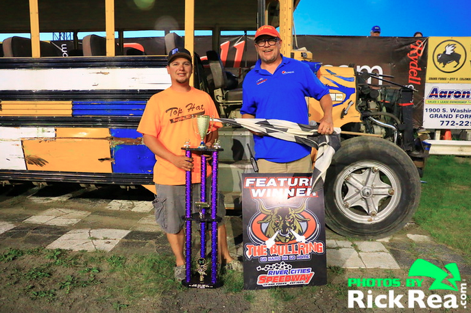 Wes Rosinski holding the trophy being interviewed by John Roberts in RydellCars.com Victory Lane at The World Famous Legendary Bullring River Cities Speedway after his commanding win in the School Bus A Main Feature Race - Photo by Rick Rea